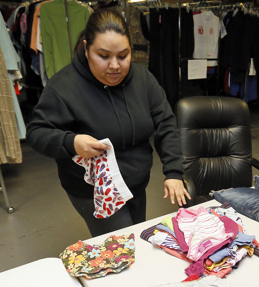 Photo - Volunteer Adriana Vasquez sorts clothes at the new Shidler-Wheeler Community Thrift Store, 735 SE 15t.   NATE BILLINGS - NATE BILLINGS