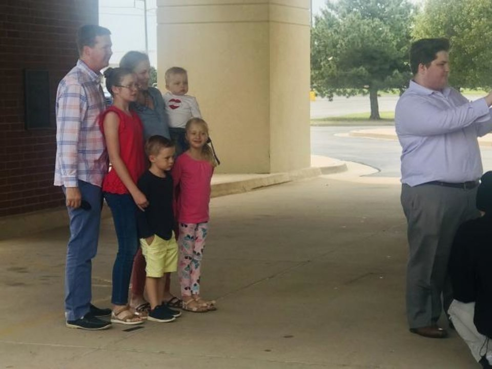 Photo -  Keenon and Andrea Deleon and their children pose for a Mother's Day family photo on Sunday as Ryan Reece, Smile Time Photo Booth photographer prepares to take their picture under the portico at Putnam City Baptist Church, 111401 N Rockwell. [Carla Hinton/The Oklahoman]