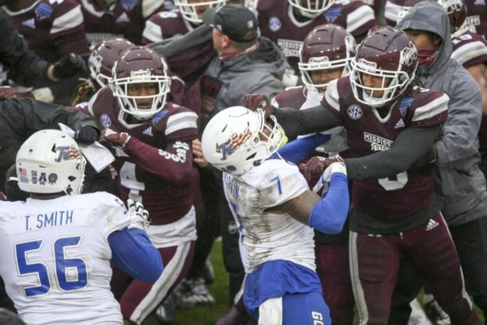 Photo -  Mississippi State linebacker Aaron Brule (3) hits Tulsa safety TieNeal Martin (7) on the facemask during a postgame fight after the Bulldogs' win in the Armed Forces Bowl on Dec. 31 in Fort Worth, Texas. [Ian Maule/Tulsa World]