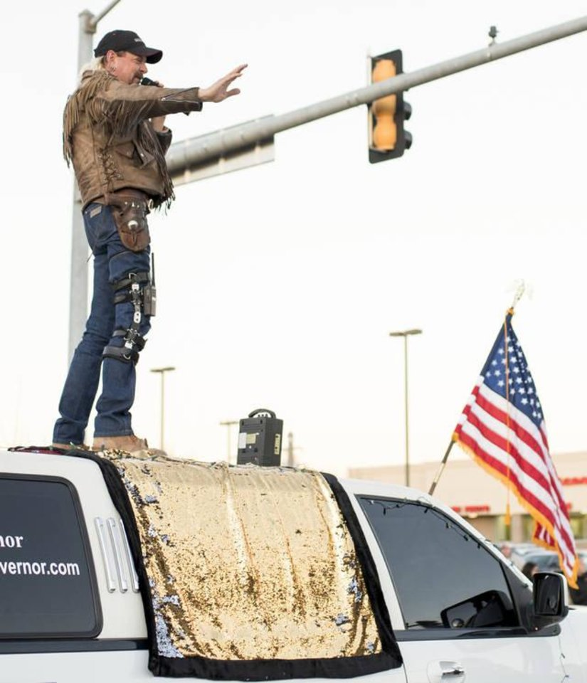 "Photo - Oklahoma gubernatorial candidate, Joseph Maldonado, known as ""Joe Exotic, waves from the top of a limousine during Norman's Christmas Parade Saturday. [WHITNEY BRYEN, FOR THE OKLAHOMAN]