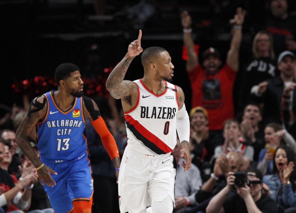 Photo - Portland Trail Blazers guard Damian Lillard, right, reacts after making a basket as Oklahoma City Thunder forward Paul George, left, trails the play during the first half of Game 1 of a first-round NBA basketball playoff series in Portland, Ore., Sunday, April 14, 2019. (AP Photo/Steve Dipaola)