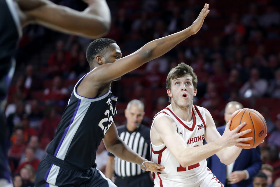 Photo - Oklahoma's Austin Reaves (12) goes past Kansas State's Montavious Murphy (23) during an NCAA college basketball game between the University of Oklahoma Sooners (OU) and the Kansas State Wildcats at Lloyd Noble Center in Norman, Okla., Saturday, Jan. 4, 2020. Oklahoma won 66-61. [Bryan Terry/The Oklahoman]