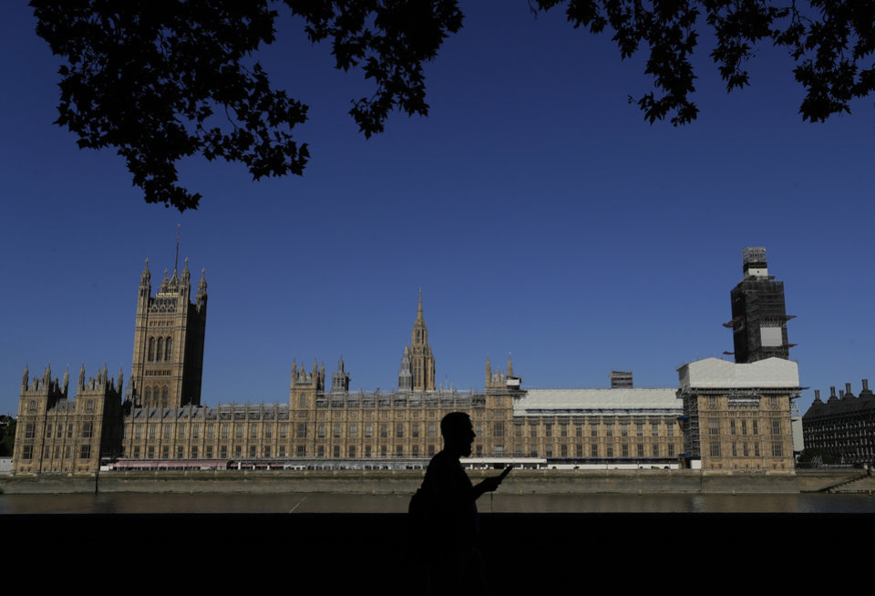 Photo -  A pedestrian passes Britain's Houses of Parliament on the bank of The River Thames in London, Thursday, Aug. 29, 2019. Jacob Rees-Mogg, The leader of the British House of Commons has defended Prime Minister Boris Johnson's move to suspend parlliament, a move that gives his political opponents less time to block a no-deal Brexit before the October 31 withdrawal deadline. (AP Photo/Kirsty Wigglesworth)