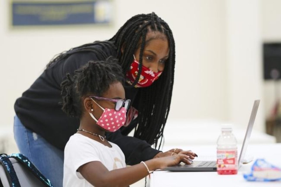 Photo -  Shariah Anderson assists student Genesis while she works Monday at the community hope center at Fifth Street Missionary Baptist Church, 801 NE 5. [Doug Hoke/The Oklahoman]