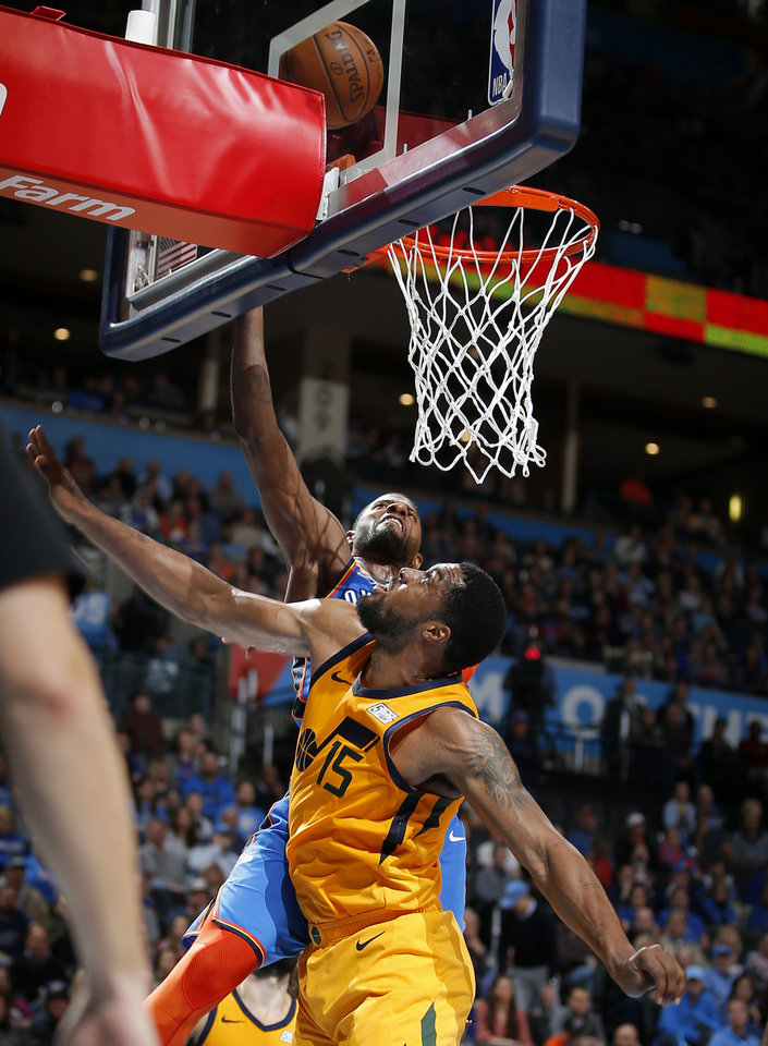 Photo - Oklahoma City's Paul George (13) shoots as Utah's Derrick Favors (15) defends during the NBA game between the Oklahoma City Thunder and the Utah Jazz at the Chesapeake Energy Arena, Friday, Feb. 22, 2019. Photo by Sarah Phipps, The Oklahoman