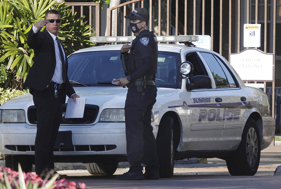 Photo -  Law enforcement personnel continue to work at an apartment complex the day after a deadly shooting in Sunrise, Fla., Wednesday, Feb. 3, 2021. Several FBI agents were killed and others wounded while trying to serve a search warrant on a child pornography suspect in Florida. FBI authorities say the suspect also died.  (Joe Cavaretta/South Florida Sun-Sentinel via AP)