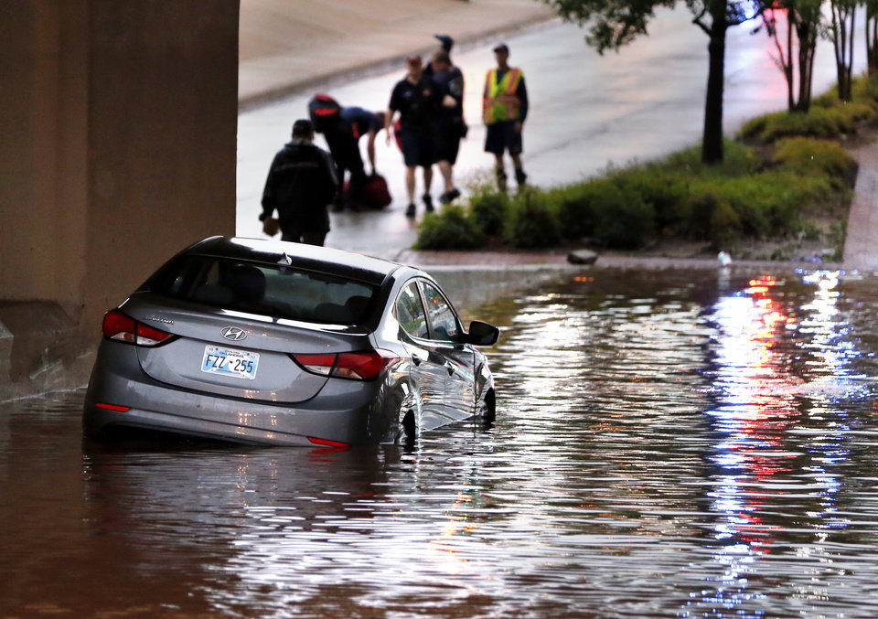 Photo -  Firefighters rescued a stranded motorist Thursday on NE 23 at the underpass of Interstate 235 as traffic was halted because of torrential rains. [Photo by Steve Sisney, The Oklahoman]
