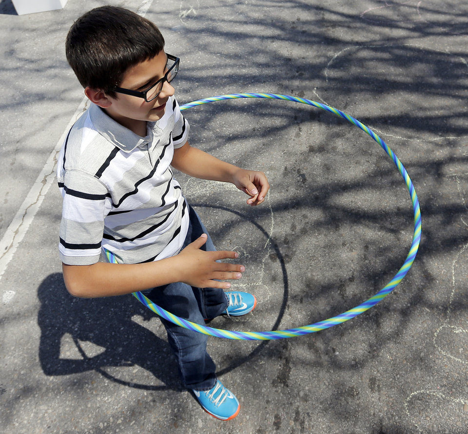 Photo - Ethan Davis, 11, hula hoops during the Open Streets OKC event along NW 23rd St. in Oklahoma City, Sunday, March 30, 2014. From noon until 4pm, NW 23rd St. between Robinson and Western was closed to cars for the event. Photo by Nate Billings, The Oklahoman