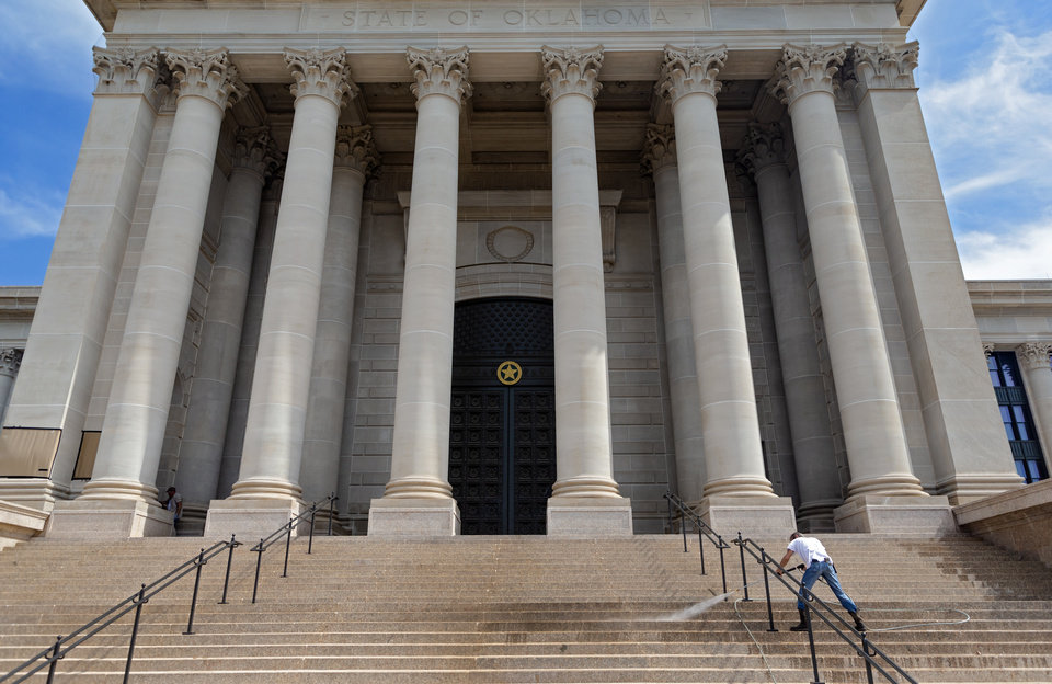 Photo - Crews uses a power washer work clean up and remove graffiti at the Oklahoma state Capitol on Monday, June 1, 2020, in Oklahoma City, Okla. that was left behind after the George Floyd protest on Sunday.    [Chris Landsberger/The Oklahoman]