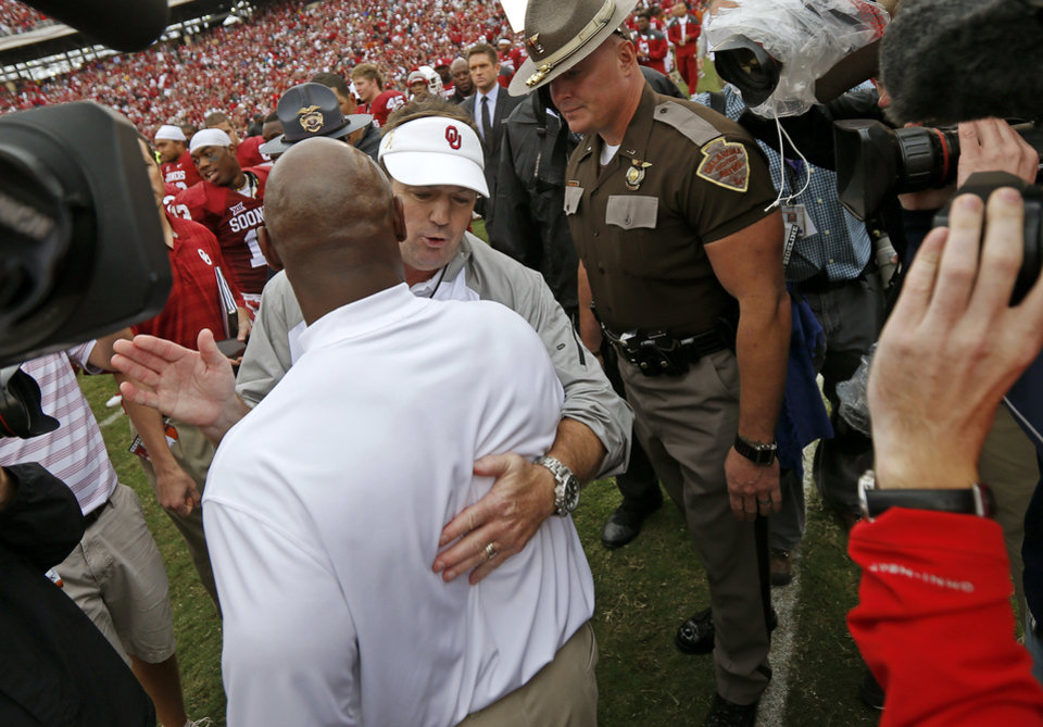 Photo - OU coach meets with Texas coach Charlie Strong after the Red River Showdown college football game between the University of Oklahoma Sooners (OU) and the University of Texas Longhorns (UT) at the Cotton Bowl in Dallas on Saturday, Oct. 11, 2014. 