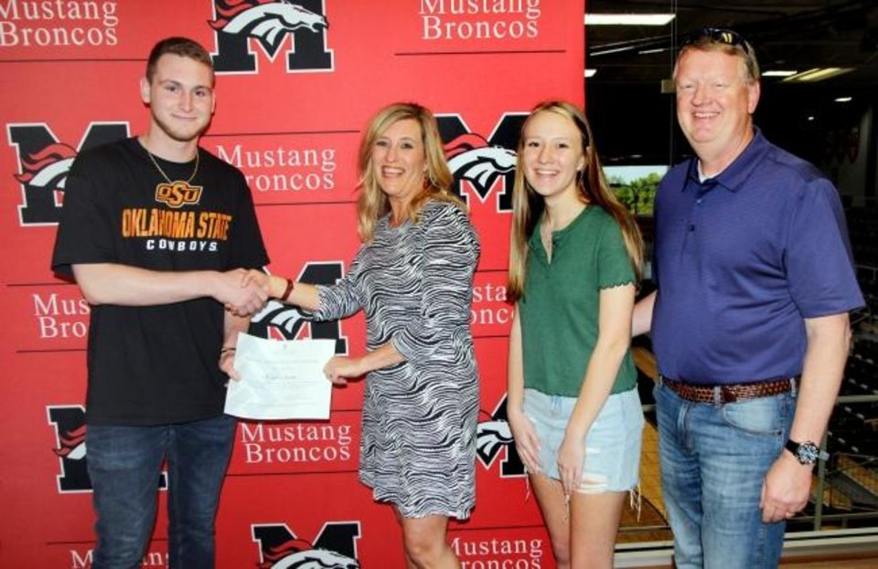 Photo -  Curtis Josey, left, receives the Bronco 4 Ever Scholarship from Stacey Scott, Callie Scott and Matt Scott, family members of Matthew George Scott IV, in whose memory the scholarship was established. [PHOTO PROVIDED]