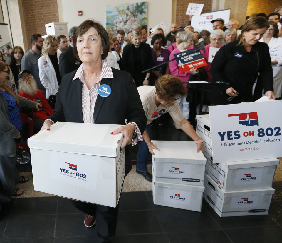 Photo - Patti Davis, president of the Oklahoma Hospital Association, carries the first box of petitions as supporters of Yes on 802, the campaign to put a Medicaid expansion state question on the ballot, deliver petitions to the Oklahoma Secretary of State's office in Oklahoma City, Thursday, Oct. 24, 2019. [Nate Billings/The Oklahoman]