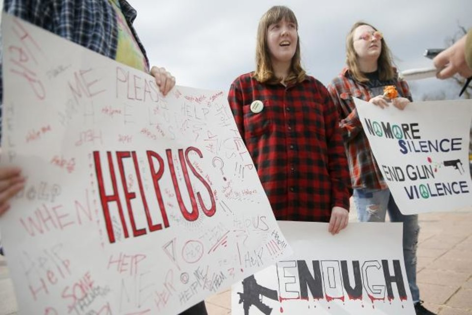 Photo -  Carissa Corcoran, 18, a senior at Putnam City West, left, and Ozlyn DelPierre, 17, a junior at Putnam City West hold signs during a March for Our Lives rally in support of gun control at the state Capitol  in Oklahoma City on Saturday. [Bryan Terry/The Oklahoman]