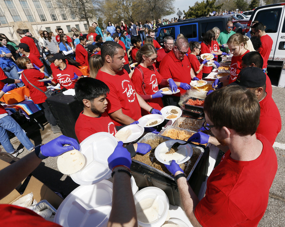 Photo - People prepare plates of free tacos from Ted's Cafe Escondido for teachers and supporters of increased education funding on the south side of the state Capitol during the eighth day of a walkout by Oklahoma teachers, in Oklahoma City, Monday, April 9, 2018. Photo by Nate Billings, The Oklahoman