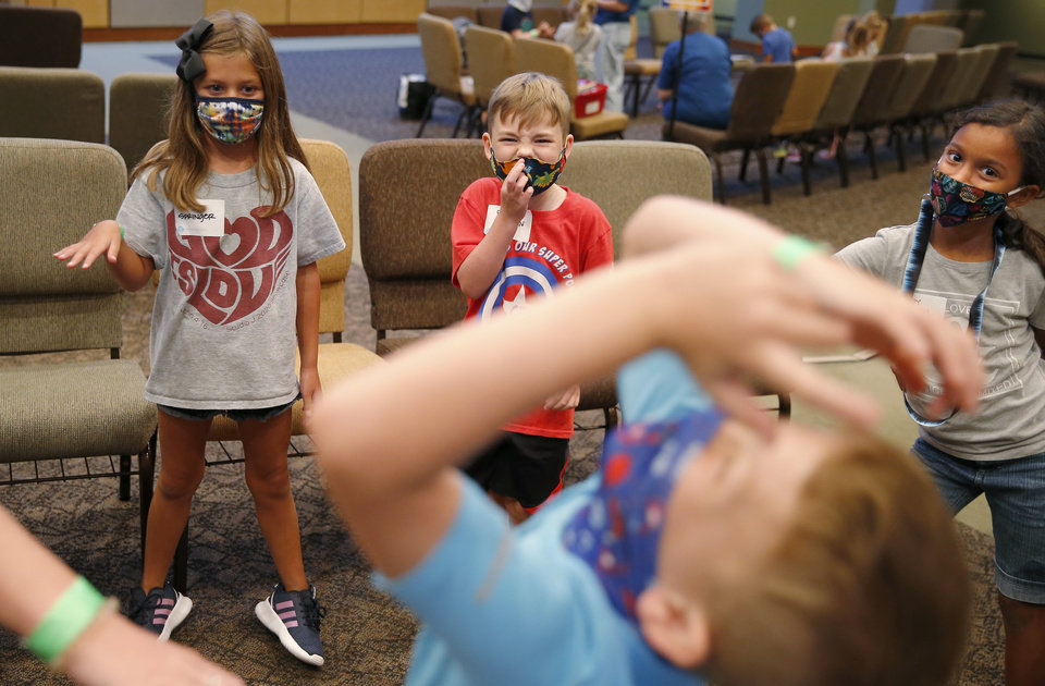 Photo - Mia Springer, 8, left, Paxton Newman, 8, and Shelby Branch, 7, play a game inside Henderson Hills Baptist Church in Edmond, Okla., Wednesday, Aug. 26, 2020. The church has begun offering Edmond school students a place to go on Wednesdays to get homework help, use the free wi-fi for virtual learning, free lunch and other activities. [Bryan Terry/The Oklahoman]