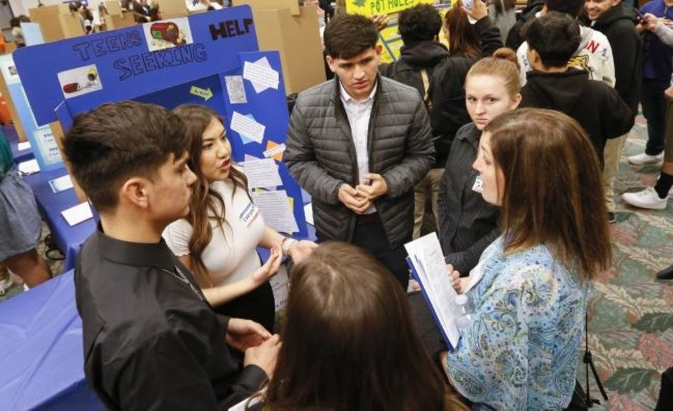 Photo -  From left, Santa Fe South High School seniors Luis Aguilar, 18, Lorena Mendoza, 18, Alvaro Guerrero, 18, and Jessica Gardner, 17, present a project about leveraging MAPS 4 to address teen drug addiction  at Generation Citizen's Civics Day at Oklahoma City Community College on Thursday. [Nate Billings/The Oklahoman]