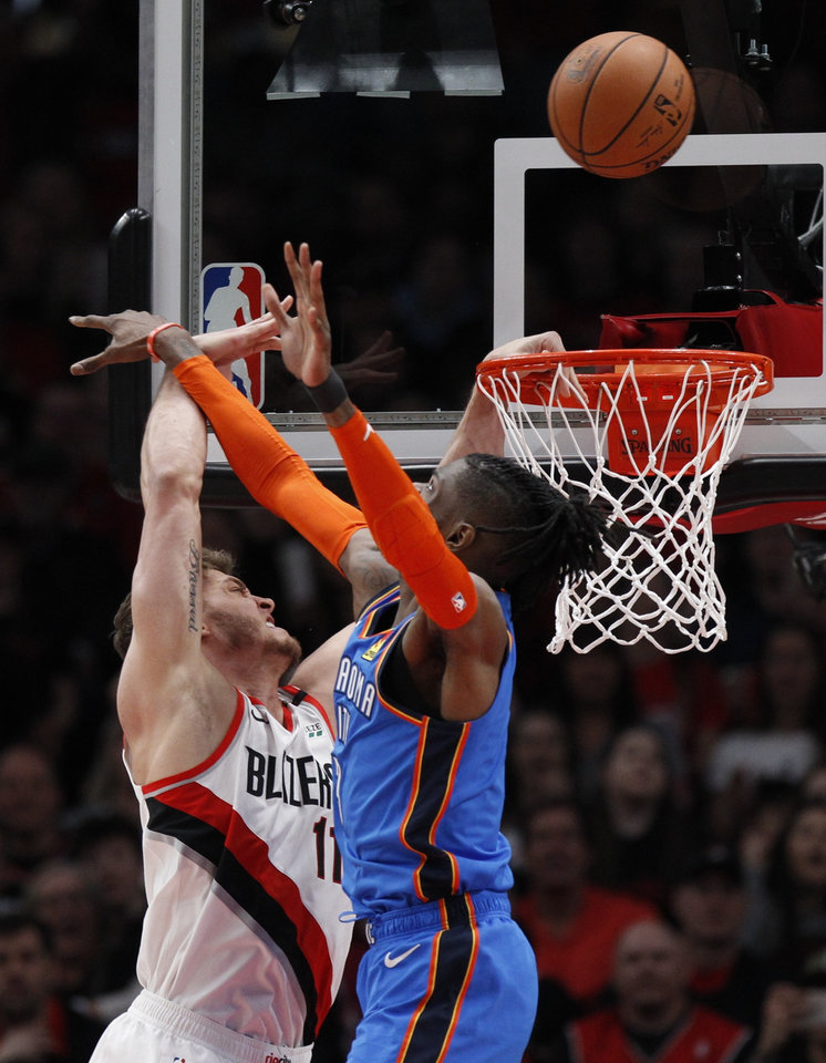 Photo - Oklahoma City Thunder forward Nerlens Noel, right, blocks the shot of Portland Trail Blazers forward Meyers Leonard, left, during the first half of Game 1 of a first-round NBA basketball playoff series in Portland, Ore., Sunday, April 14, 2019. (AP Photo/Steve Dipaola)