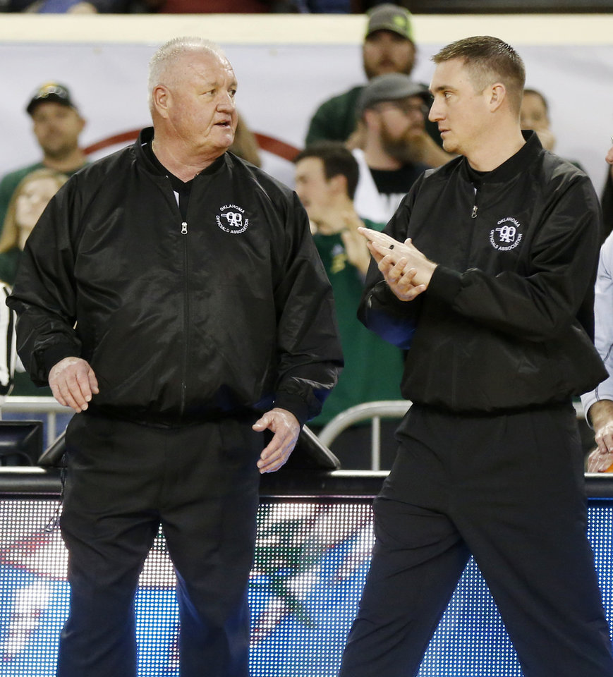 "Photo - Officials Mark Martin, left, and Dakota Martin talk before a Class A boys high school basketball semifinal game in the state tournament between Stuart and Arapaho-Butler inside Jim Norick Arena, ""The Big House,"" at State Fair Park in Oklahoma City, Friday, March 6, 2020. The two are the first father and son to officiate a game together in the state tournament. [Nate Billings/The Oklahoman]"