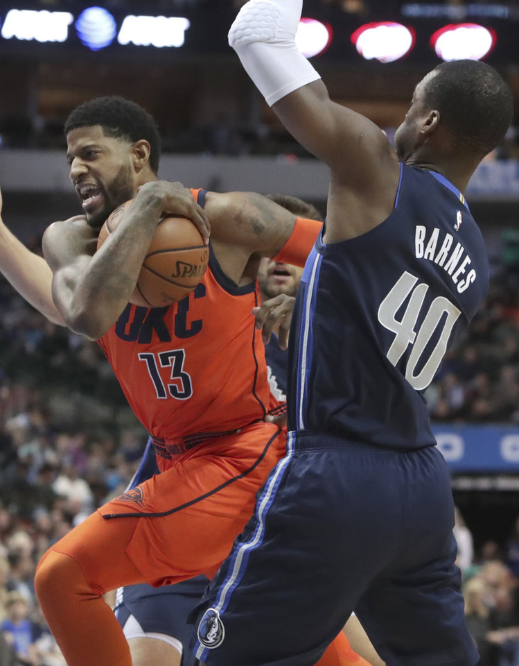 Photo - Oklahoma City Thunder forward Paul George (13) tries to get past Dallas Mavericks defenders Harrison Barnes (40) during the first half of an NBA basketball game in Dallas, Sunday, Dec. 30, 2018. (AP Photo/LM Otero)