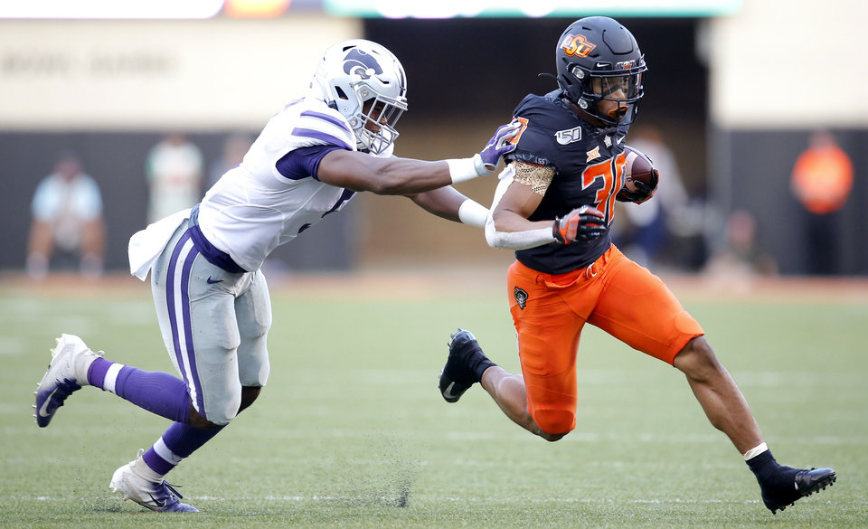 Photo - Oklahoma State's Chuba Hubbard (30) is pushed by Kansas State's Da'Quan Patton (5) during the college football game between the Oklahoma State Cowboys and the Kansas State Wildcats at Boone Pickens Stadium in Stillwater, Okla., Friday, Sept. 27, 2019. [Sarah Phipps/The Oklahoman]