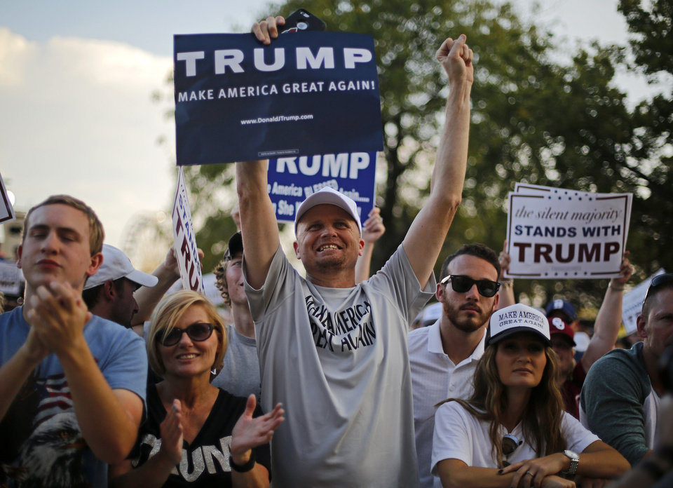 Photo - Justin Maddix of Elk City, center, holds a sign for Donald Trump during the Republican presidential candidate's rally at the Oklahoma State Fair in Oklahoma City, Friday, September 25, 2015. Photo by Bryan Terry, The Oklahoman