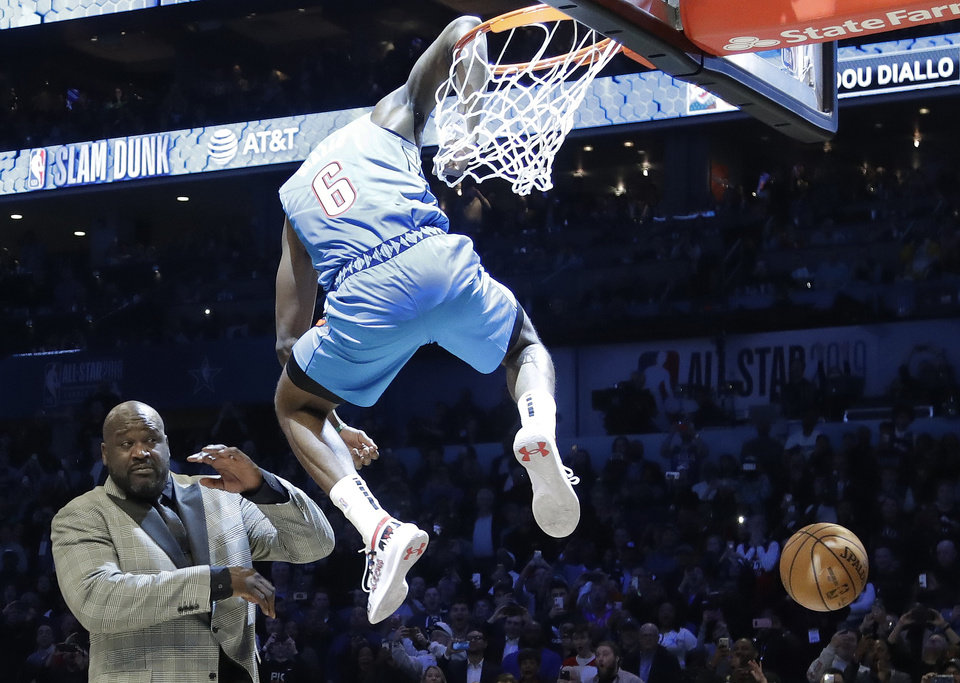Photo - Oklahoma City Thunder Hamidou Diallo leaps over former NBA player Shaquille O'Neal during the NBA All-Star Slam Dunk contest, Saturday, Feb. 16, 2019, in Charlotte, N.C. Diallo won the contest. (AP Photo/Chuck Burton)