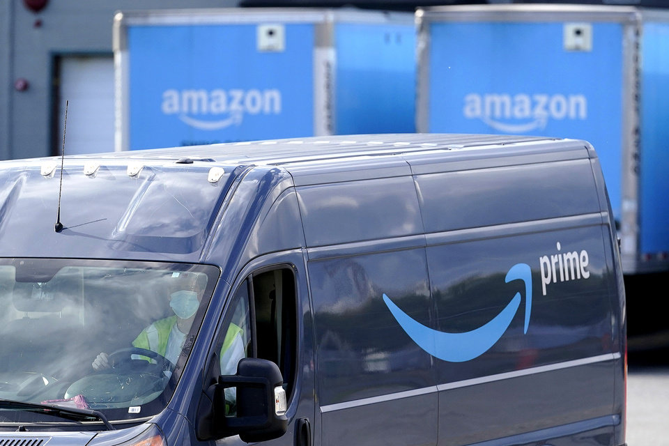 Photo -  FILE - In this Oct. 1, 2020 file photo, an Amazon Prime logo appears on the side of a delivery van as it departs an Amazon Warehouse location in Dedham, Mass.  Amazon, is one of the few companies that has thrived during the coronavirus outbreak. People have turned to it to order groceries, supplies and other items online, helping the company bring in record revenue and profits between April and June. That came even though it had to spend $4 billion on cleaning supplies and to pay workers overtime and bonuses.   (AP Photo/Steven Senne, File)