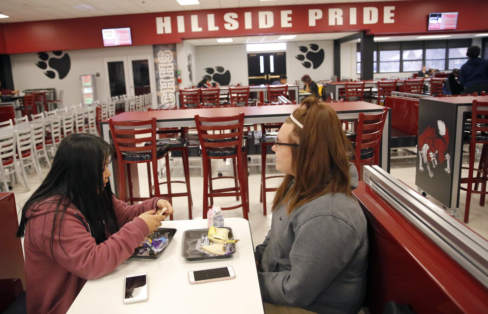 Photo -  Asia Herrera, right, and Dal Sung eat a late-afternoon meal at Capitol Hill High School on Thursday. [Photo by Sarah Phipps, The Oklahoman]
