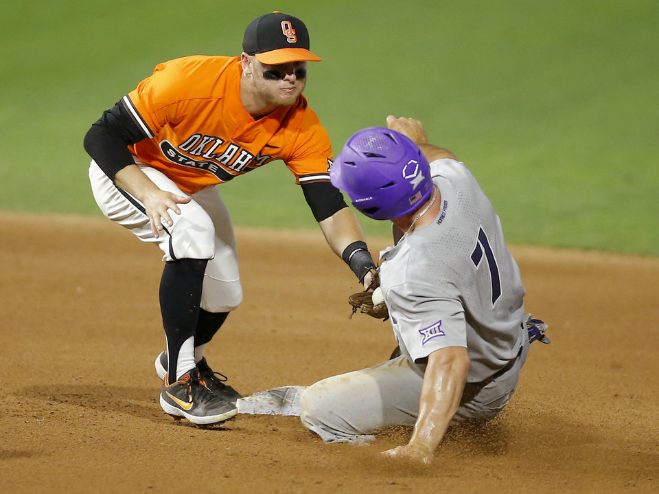 Photo - Oklahoma State's Andrew Navigato (4) tags TCU's Josh Watson (7) at second base in the sixth inning of a Big 12 baseball tournament game between Oklahoma State University (OSU) and TCU at Chickasaw Bricktown Ballpark in Oklahoma City, Okla., Wednesday, May 22, 2019.  [Bryan Terry/The Oklahoman]