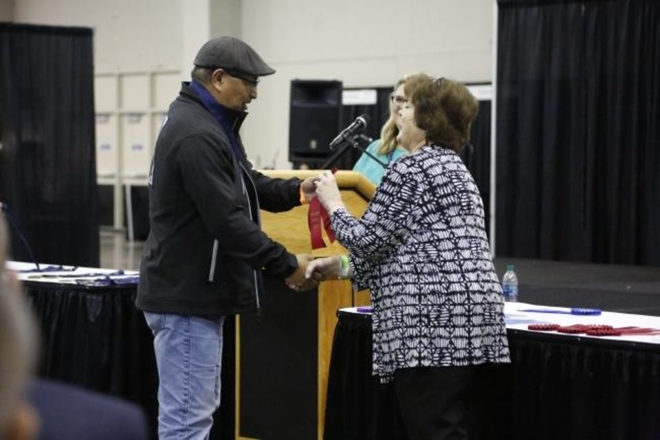 Photo -  Randy Kemp receives his ribbon for his second-place finish in waterbased painting from Red Earth Board President Lona Barrick during the 2019 Red Earth Festival at the Cox Convention Center in Oklahoma City, Oklahoma Friday, June 7, 2019. [Paxson Haws/The Oklahoman]
