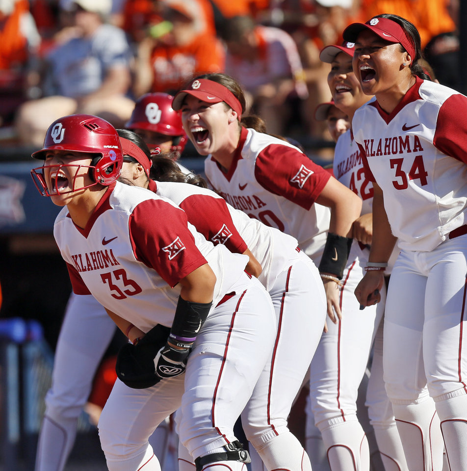 Photo - The Sooners react as Nicole Pendley (1), not pictured, runs the bases after hitting a two-run home run in the fifth inning during the championship game of the Big 12 softball tournament between Oklahoma and Oklahoma State (OSU) at ASA Hall of Fame Stadium in Oklahoma City, Saturday, May 13, 2017. OU won 2-0. Photo by Nate Billings, The Oklahoman