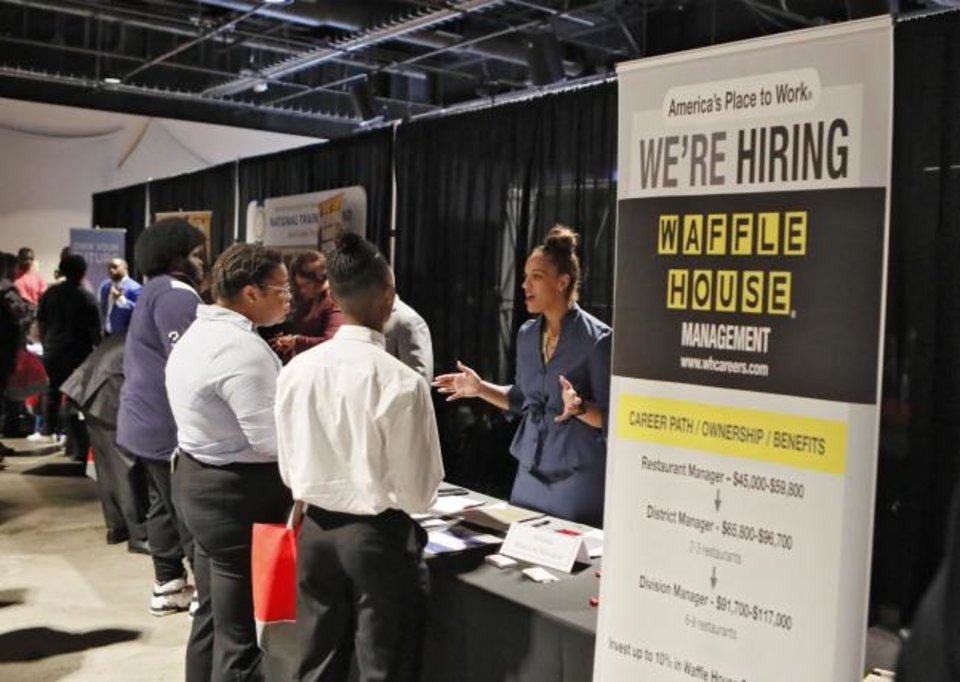 Photo -  A Waffle House representative speaks to potential applicants during a job and resource fair in Atlanta. [AP PHOTO]