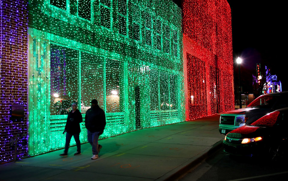Photo -  Pedestrians walk by Lights on Broadway, Automobile Alley's holiday lights, is part of Downtown in December.  [Photo by Doug Hoke, The Oklahoman]