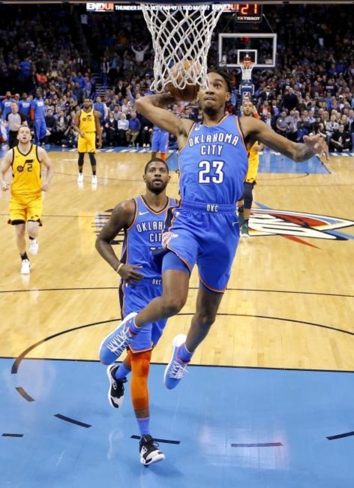 Photo -  Oklahoma City's Terrance Ferguson goes up for a dunk in front of teammate Paul George during Friday night's double overtime victory against Utah. [Sarah Phipps/The Oklahoman]