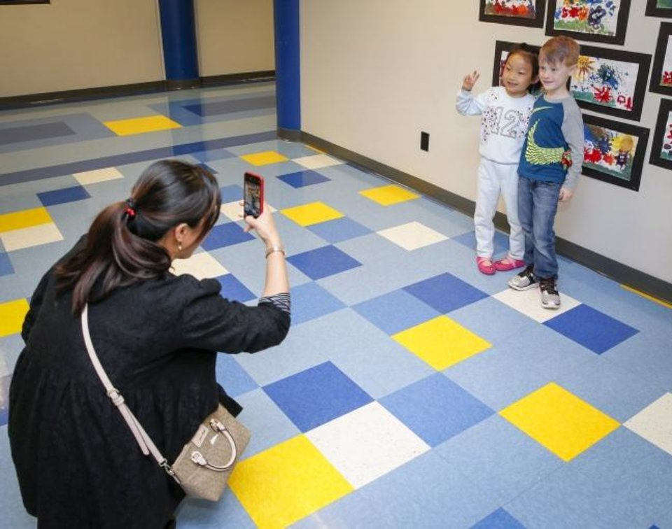 Photo -  Angela Chen takes a photo of her daughter, Coco Chen, 6, at left, and Canyon Vaught, 6,  after finishing a tour Saturday at Eugene Field Elementary. Coco and Canyon are both at Gatewood this year and will be entering first grade. [Nate Billings/The Oklahoman]