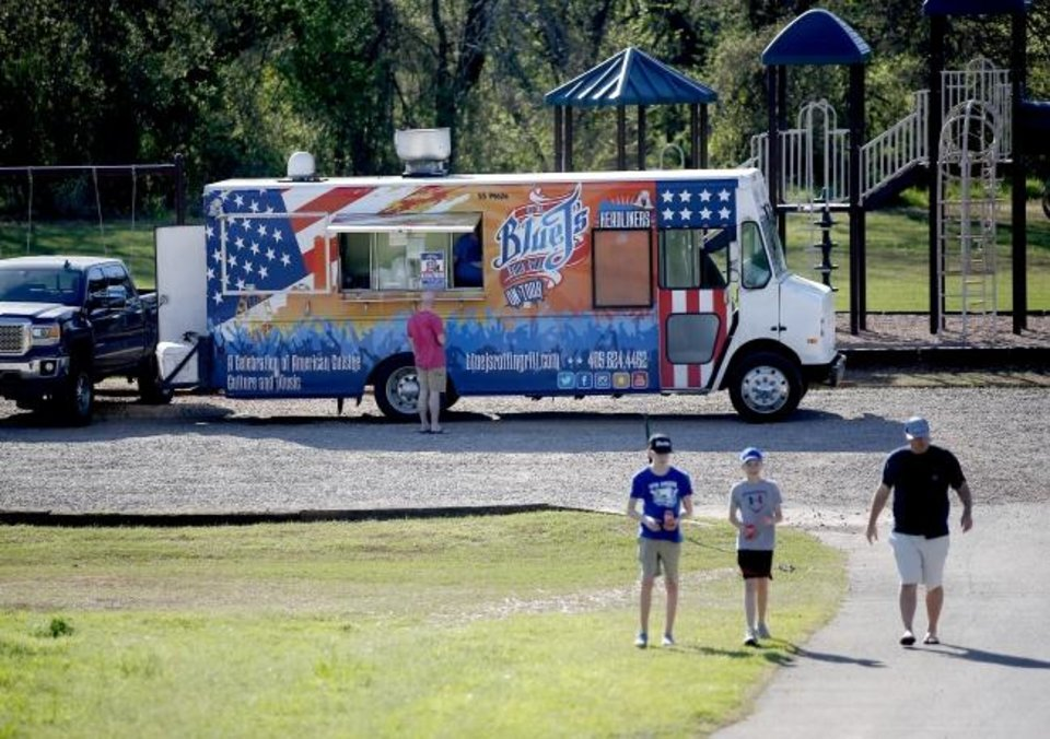 Photo -  People wait for their orders Tuesday at the Blue J's Rollin' Grill food truck at the park in The Ridge neighborhood in Edmond. [Sarah Phipps/The Oklahoman]