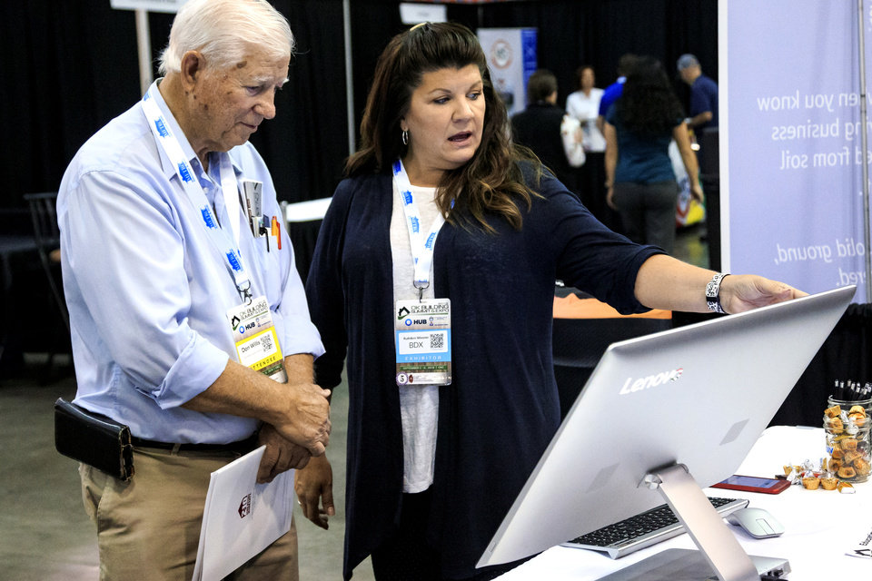 Photo -  RuthAnn Wiesner with BDX talks with homebuilder Don Willis during the Oklahoma Building Summit at Cox Convention Center. [PHOTO BY CHRIS LANDSBERGER, THE OKLAHOMAN]