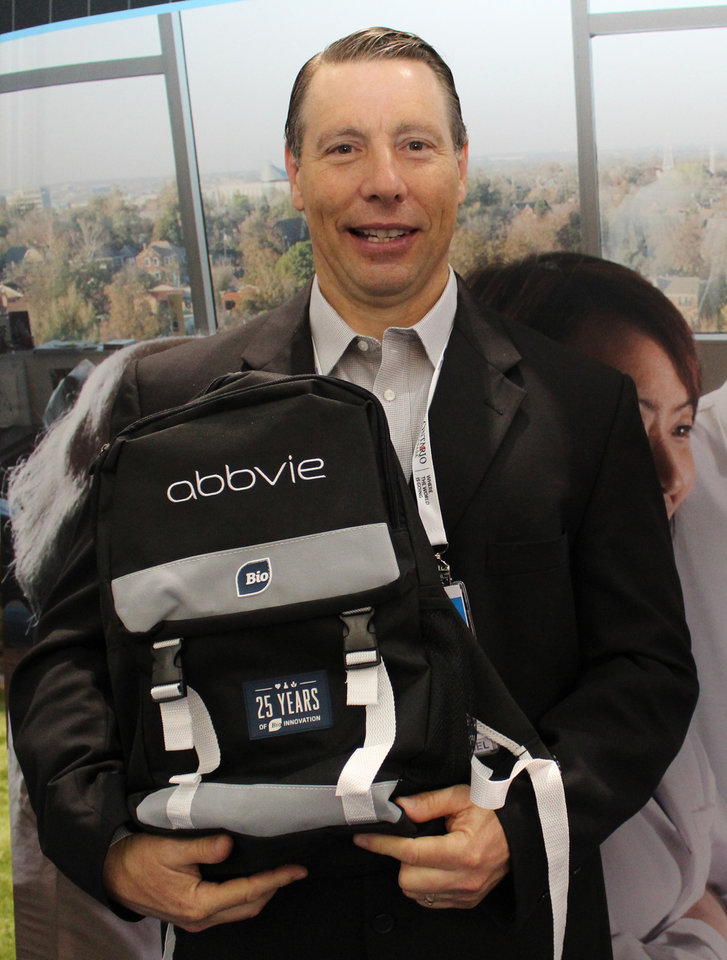 Photo -  William Hildebrand, founder and chief scientist with Oklahoma City's Pure MHC, holds a backpack branded with the AbbVie name, a major pharmaceutical company that has signed a licensing deal with his company.
