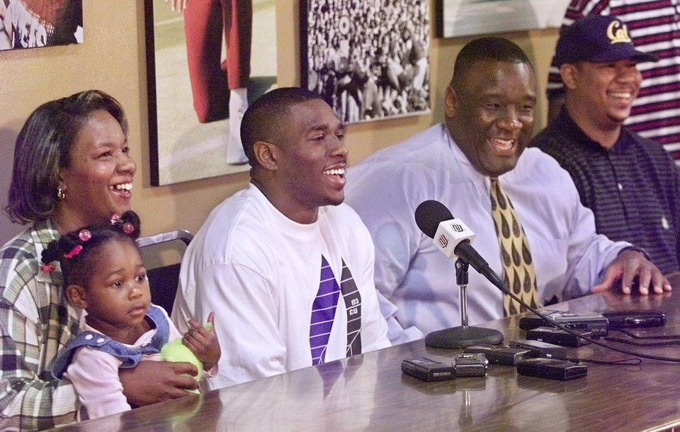 Photo - De'Mond Parker makes the announcement of his availability for the NFL draft. With Parker, from left, is his mom, Carol Parker, holding De'Mond's daughter Dominique, 2, OU football coach John Blake,  and his older brother, Dyrel Parker.