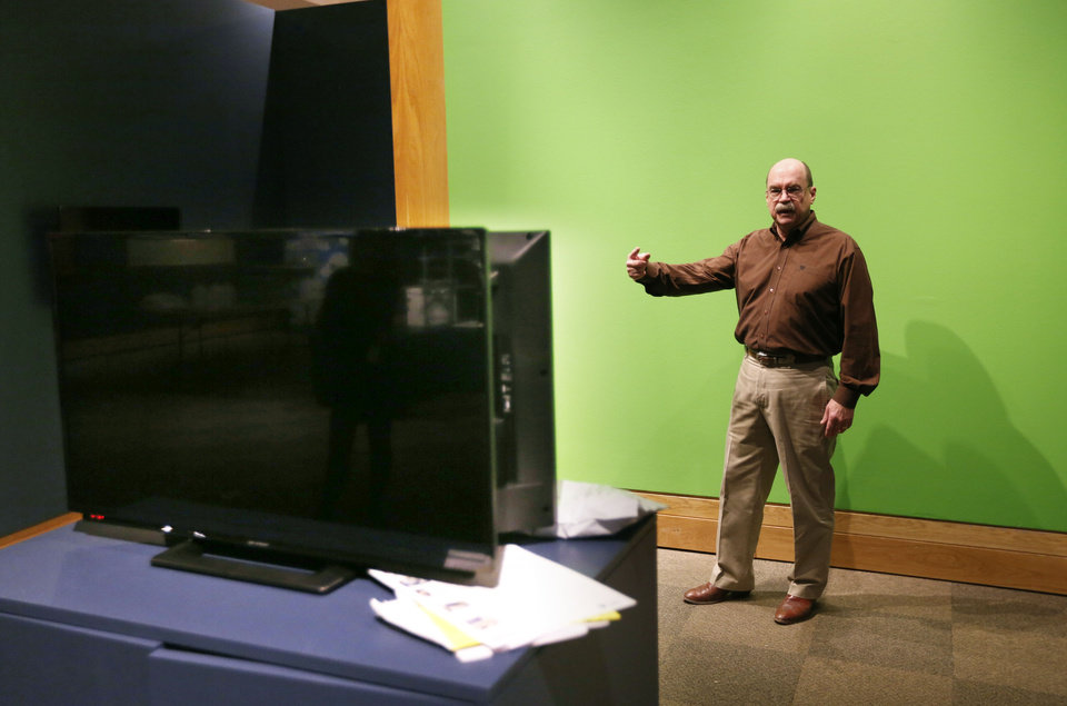 Photo -  Don Reeves, who holds the McCasland Chair of Cowboy Culture at the National Cowboy & Western Heritage Museum, demonstrates the TV weather forecaster's green screen that is part of the exhibit