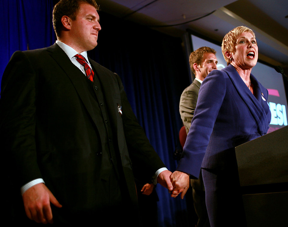 Photo - Holding hands with her sons Joe (left) and Ben, Janet Barresi speaks to a crowd during the Republican Watch Party at the Marriott in Oklahoma City on Tuesday, Nov. 2, 2010.Photo by John Clanton, The Oklahoman
