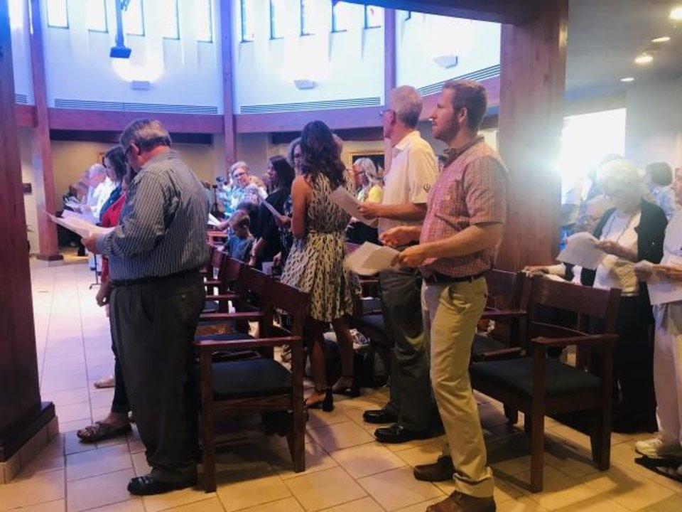 Photo -  Guests sing a hymn at a Mass marking the 60th anniversary of the Rev. Marvin Leven's ordination on May 16 at St. Ann's Retirement Center in Oklahoma City,. [Carla Hinton/The Oklahoman]