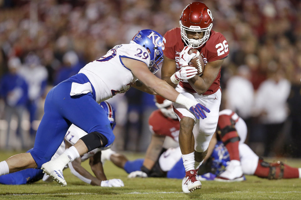 Photo - Oklahoma's Kennedy Brooks (26) tries to get past Kansas' Joe Dineen Jr. (29) during a college football game between the University of Oklahoma Sooners (OU) and the Kansas Jayhawks (KU) at Gaylord Family-Oklahoma Memorial Stadium in Norman, Okla., Saturday, Nov. 17, 2018. Photo by Bryan Terry, The Oklahoman