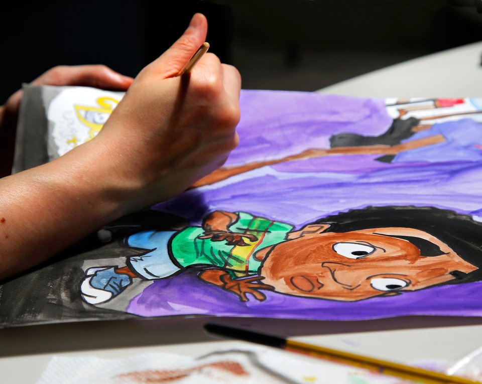 Photo -  Michelle Cross paints a poster. [Photo by Jim Beckel, The Oklahoman]