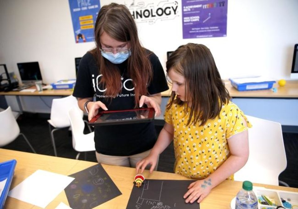 Photo -  Madeline Peck, right, and Kayla Lakey make a stop-motion video Thursday at iCode Edmond. [Sarah Phipps, The Oklahoman]