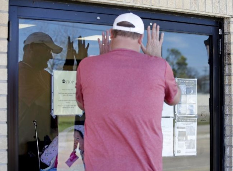 Photo -  Mike Nunley waves to his wife, Becky, through the glass doors of Grace Living Center in Bethany. The district athletic director for Edmond Public Schools can only see her through the windows of the facility, which is closed to visitors during the coronavirus pandemic. [SARAH PHIPPS/THE OKLAHOMAN]