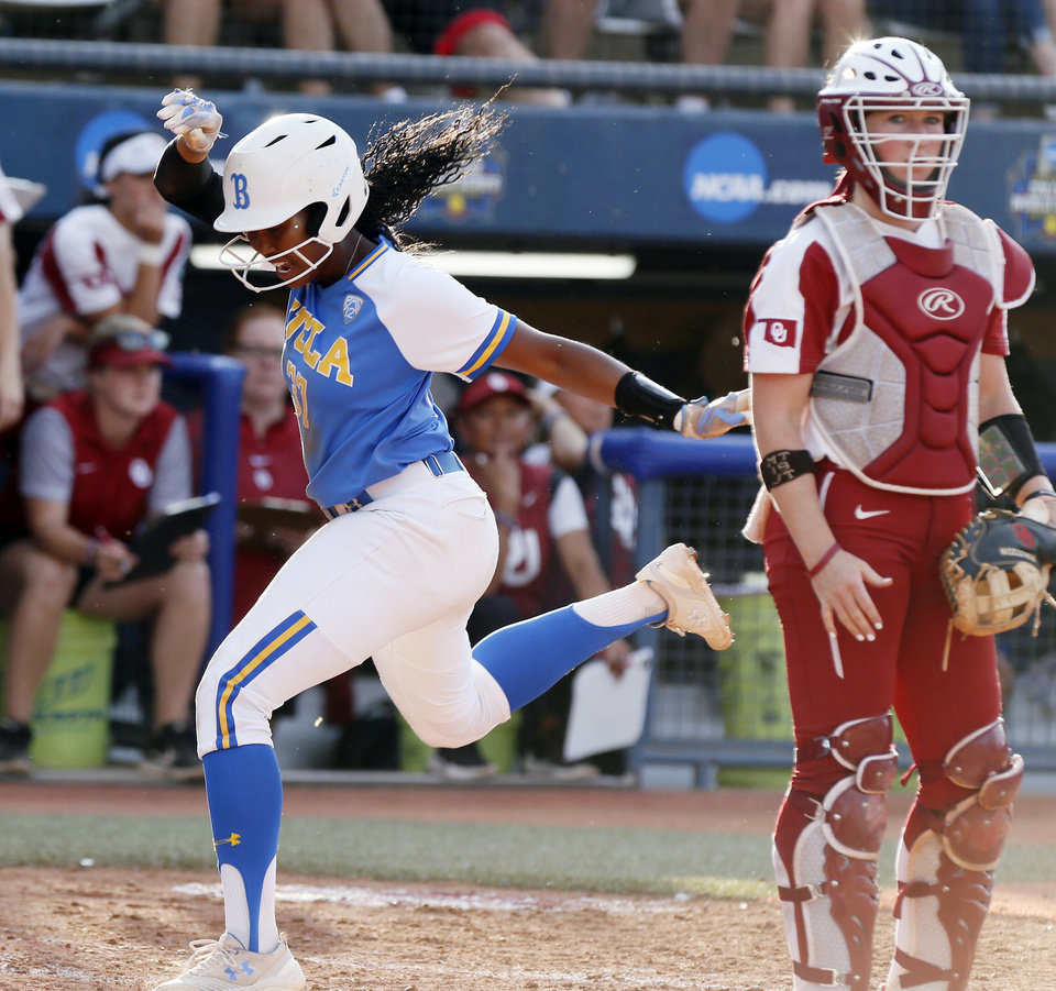 Photo - UCLA's Kinsley Washington (37) scores in the third inning next to OU catcher Lynnsie Elam (22) during the first NCAA softball game in the championship series of the Women's College World Series between Oklahoma and UCLA at USA Softball Hall of Fame Stadium in Oklahoma City, Monday, June 3, 2019. [Nate Billings/The Oklahoman]