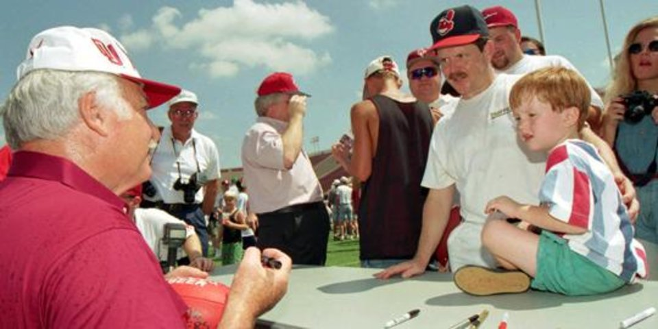 Photo -  OU head football coach Howard Schnellenberger autographs a football for Sam Albertson and his son Tyler, 3, of Norman in 1995.