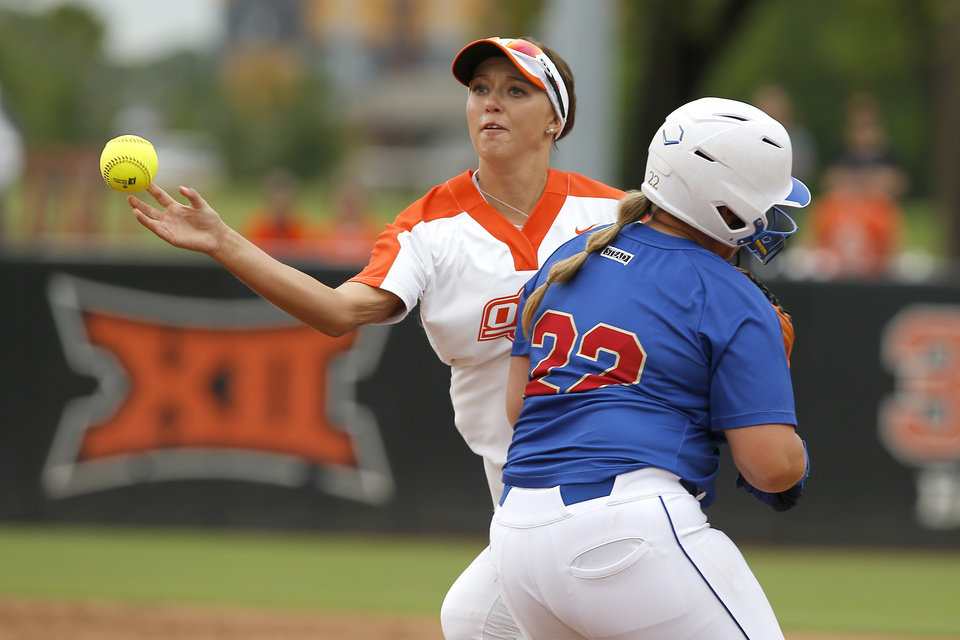 Photo - Oklahoma State's Madi Sue Montgomery (10) throws back to first for an out as she collides with Tulsa's Rylie Spell (22) during the seventh inning of the Stillwater Regional NCAA softball tournament game between Oklahoma State University (OSU) and Tulsa in Stillwater, Okla., Saturday, May 18, 2019. Oklahoma State won 2-1. [Bryan Terry/The Oklahoman]