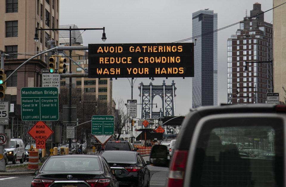 Photo -  The Manhattan bridge is seen, Thursday, in the background of a flashing sign urging commuters to avoid gatherings, reduce crowding and to wash hands in the Brooklyn borough of New York. [Wong Maye-E/Associated Press File Photo]